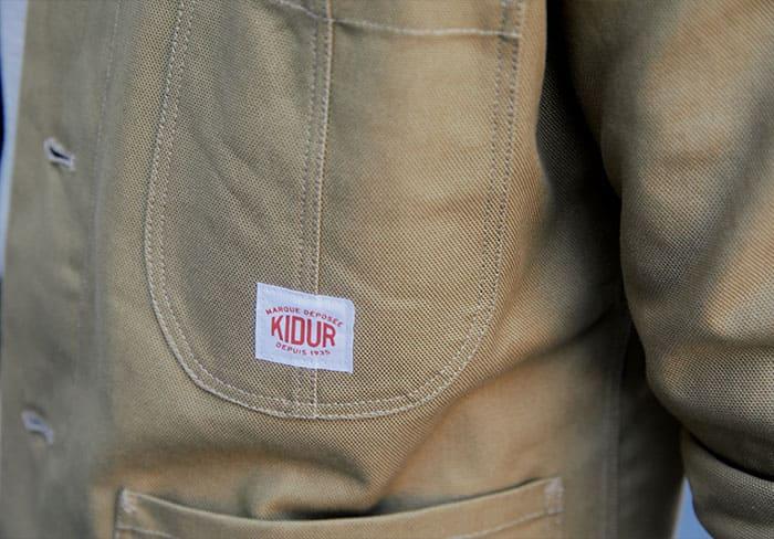 Poche extérieur de la Train Natté Kaki est composé d'un logo Kidur
